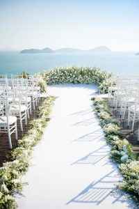 White floral alter with ocean backdrop