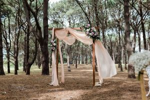 Soft chiffon floral arches in woodland setting