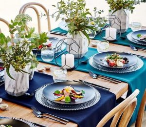 Set table with blue ombre linen and marble vases