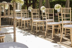 Beach wood chairs with small bouquets of white flowers