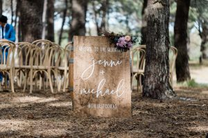 vintage wedding sign sitting in the woods