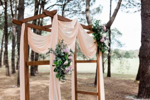 wooden arch with pink draping on woodland setting