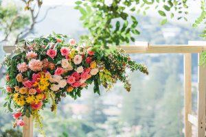 Flower arrangement on top of wedding arches